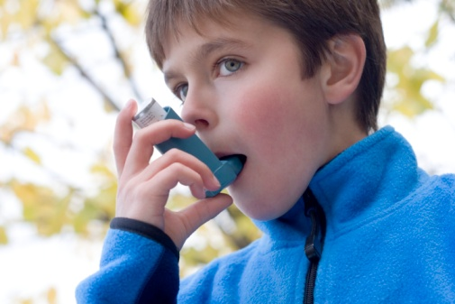 Boy (10-11) using inhaler